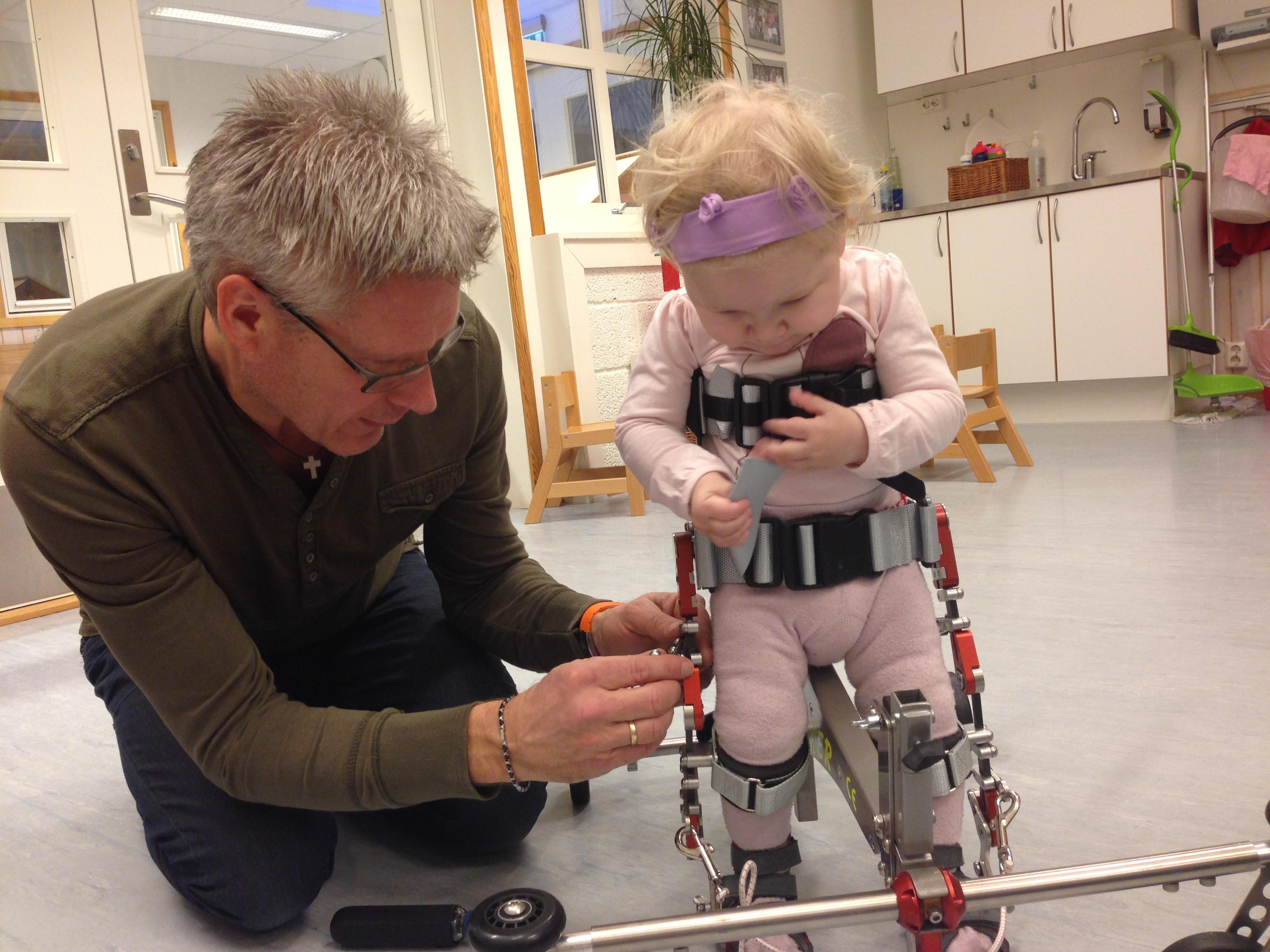 Sara 15 months walking in assistive device