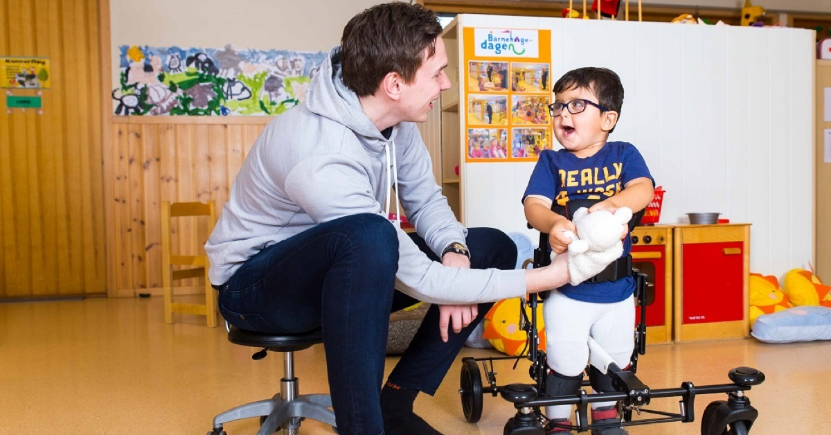 Physiotherapist and a boy with disability in a gait trainer