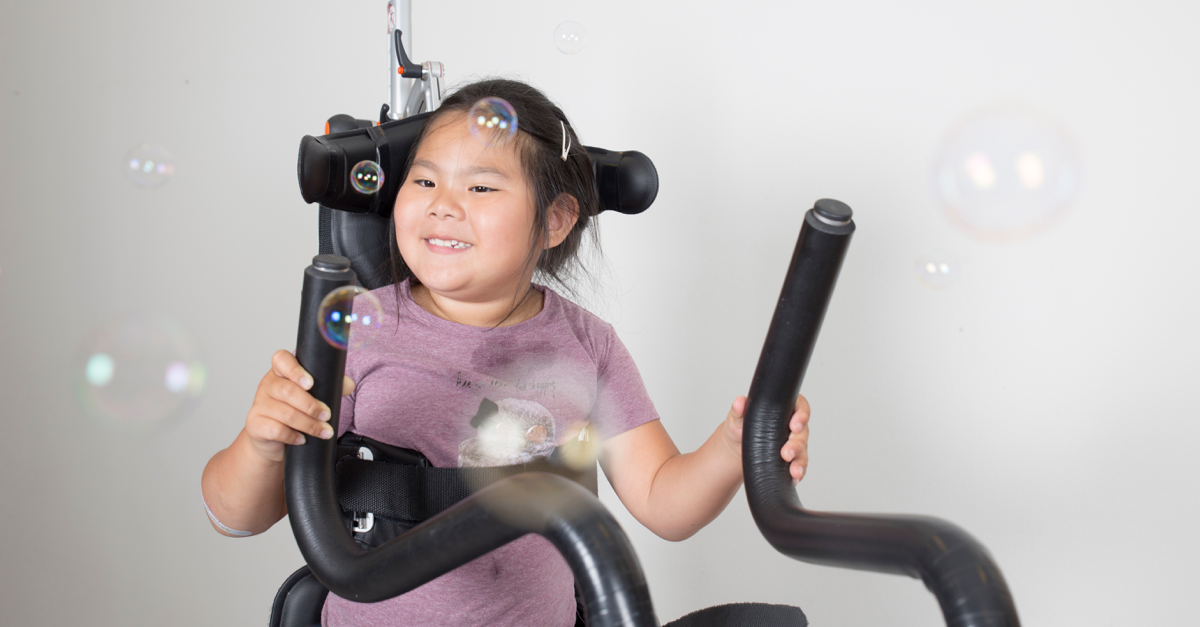 Girl in assistive device and bobles!  Hwat do we know about physical activity and cerebral palsy?