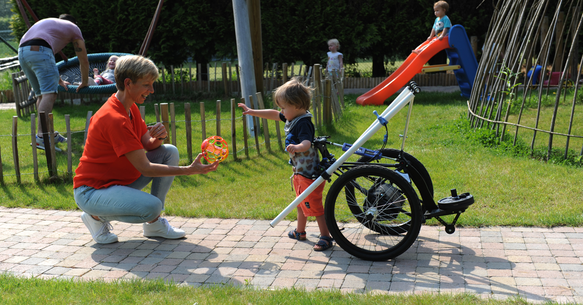 Ria Cuppers playing in the park with a small boy in his Hibbot assitive device