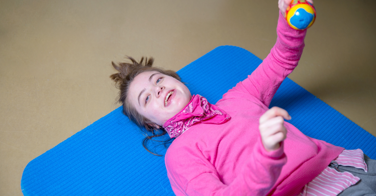 Girl with disabilities lying on the floor smiling