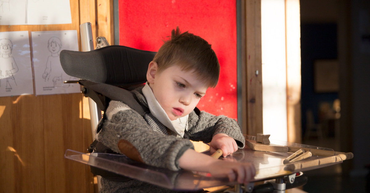 Boy with disability sitting in assitive device.