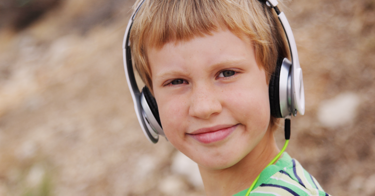 Blonde boy with headphones. Music therapy for kids with disabilities
