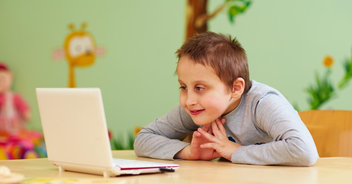 Gutt med funksjonsnedsettelse som ser på dataskjerm. Nyttige teknologier og hjelpemidler for personer med funksjonsnedsettelser