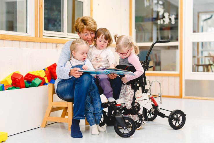 Girl stands in her NF-Walker and reading a book with her friends