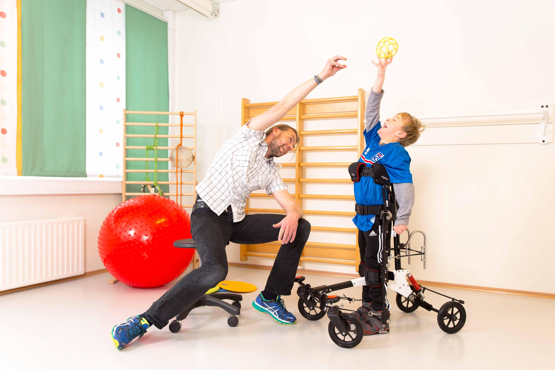 Älterer Junge mit persönlicher Betreuerin beim Spielen im NF-Walker
