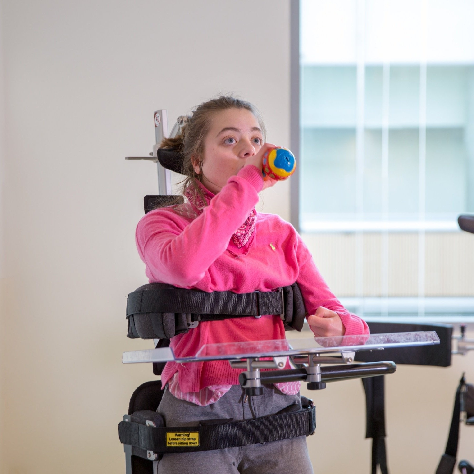 Girl in assistive device. Dressed in pink playing with a toy.