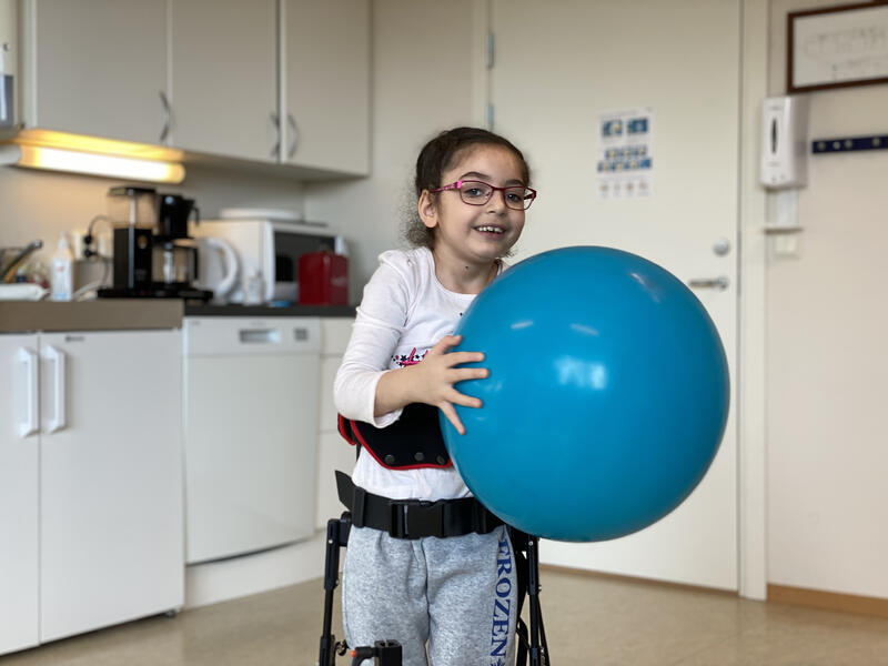 Young girl playing with big blue ball while standing in NF-Walker