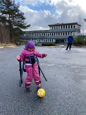Ung jente spiller fotball med hjelp og støtte fra Hibbot