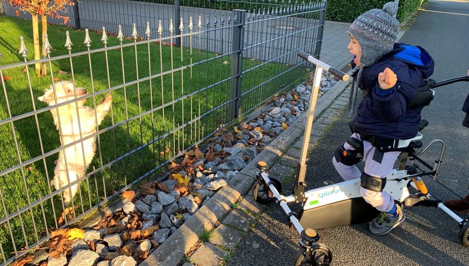 Ung pojke står i sin Xplore och njuter av utsikten av hunden bakom staketet