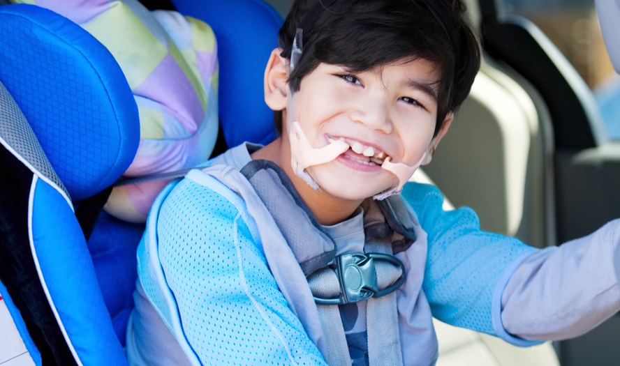 Gutt med funksjonsnedsettelse som sitter i en bil klar for ferie